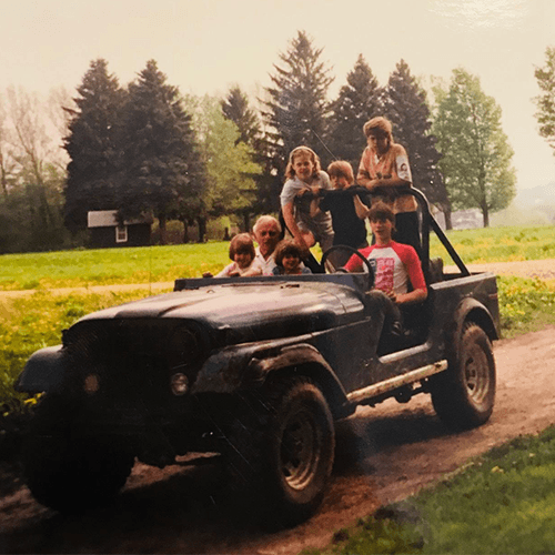 photo from 1990's people sitting in jeep, three people in front row and three people in back row standing in hermatige, NY