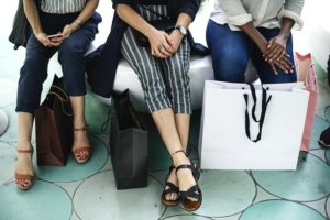 young people sitting on bench with shopping bags in front of their legs