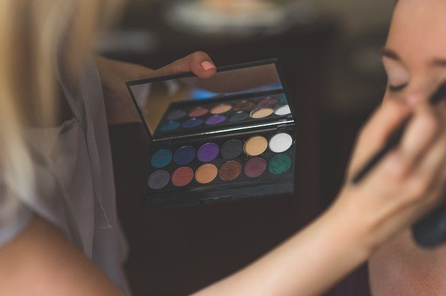 Make-up artist applying blush to client for a photoshoot for her website