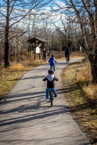 Child riding bike on bike path in park in Plattsburgh, NY in the fall.