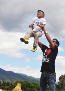 Man in black shirt holding smiling child in air in front of adirondack mountains in fall