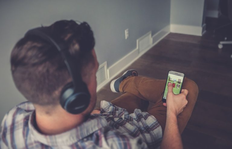 man wearing headphones wearing plaid looking at website on cell phone