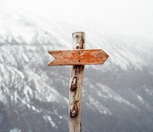 adirondack mountain in background covered in snow with wooden signpost in the foreground
